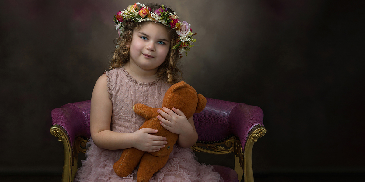 portrait of child wearing pink dress, holding teddy bear